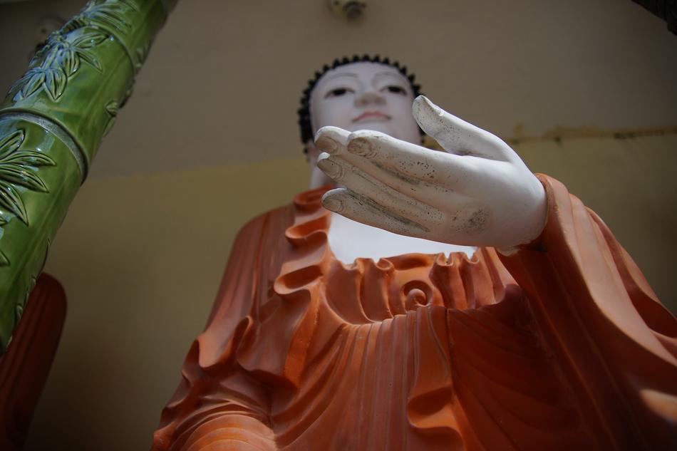 An upwards perspective shot of a Buddha's hand.