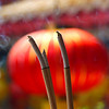 Burning incense sticks with colourful paper lanterns blurred out in the background.