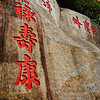 Colourful red Chinese characters engraved into the rock.