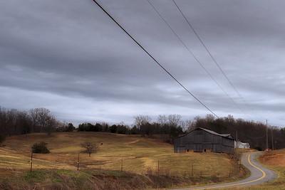 Barn and field near winding narrow country road
