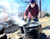 Peter Gould, of Brattleboro, Vt., sifts off some of the debris from the boiling sap while sugaring in his backyard on Friday, March 19, 2021.