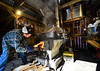 Zach Clark, of Brattleboro, Vt., stokes the fire while sugaring inside his father's backyard sugar shack, in Vernon, Vt., on Monday, March 22, 2021.