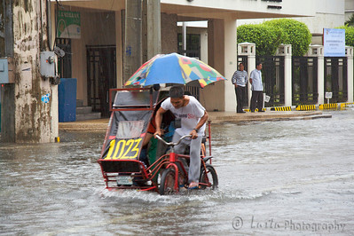 Images taken in Manila a few hours after the typhoon Frank (fengshen) hit the capital of Philippines. Tricyclist riding under heavy rain in the middle of a flooded boulevard
