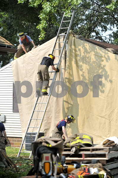 -Messenger photo by Hans Madsen<br /> <br /> Before igniting the old structure for the final time firefighters cover the neighboring home with tarps to protect it from radiant heat. During the fire, the also sprayed water on it.
