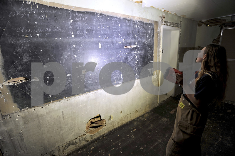 -Messenger photo by Hans Madsen<br /> <br /> Badger firefighter Kayla Sterler looks over an old chalkboard painted on the wall inside the building burning for training Saturday. There were still spelling word lists on it. It was uncovered when crews removing asbestos removed a layer of drywall.