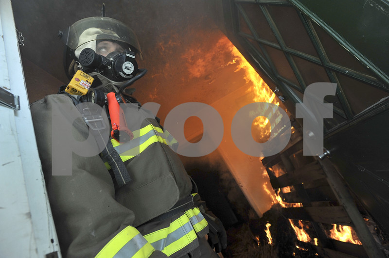 -Messenger photo by Hans Madsen<br /> <br /> Badger firefighter Jason Smith keeps an out towards the exterior of the house as the freshly set fire gets going behind him.