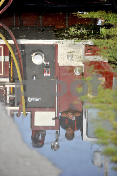 -Messenger photo by Hans Madsen<br /> <br /> Badger firefighter Chris Vendell is reflected in a puddle of water Saturday morning as he operates one of the department's pumper trucks.