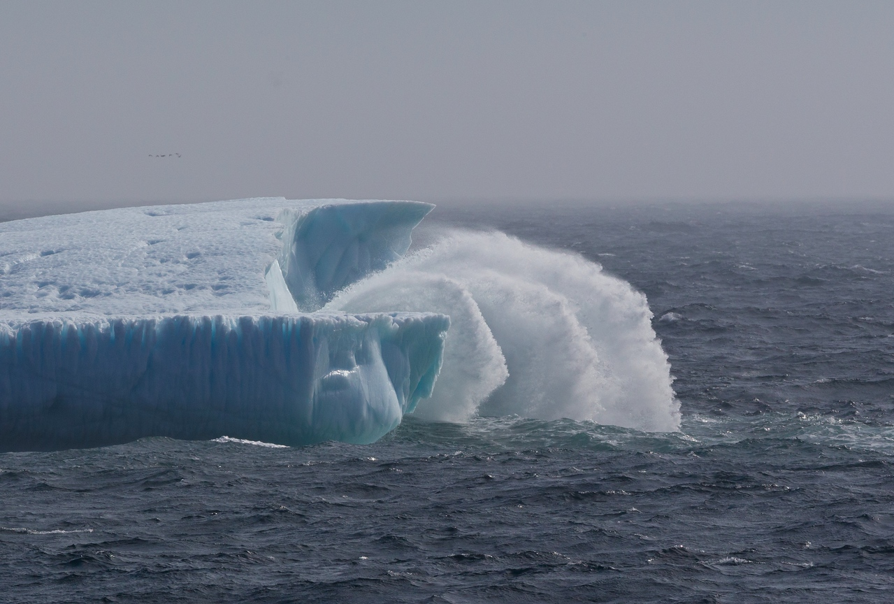 Rough seas breaking against a huge iceberg in Davis Strait
