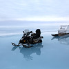 Snowmobile and qamutik on the sea ice with a layer of melt water on the surface