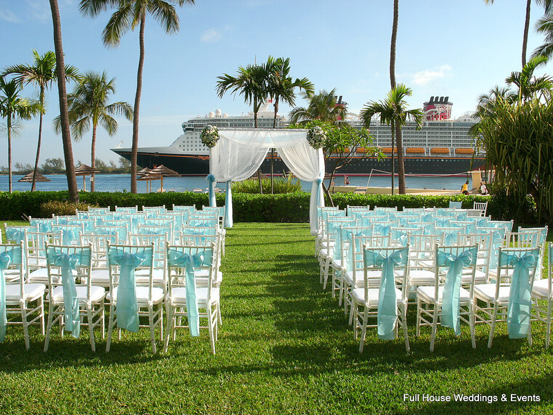 Ceremony in the garden overlooking the harbour at British Colonial Hilton - Arbor draped in sheer white and tiffany blue fabric with floral clusters. White chaivari chairs with tiffany ties.