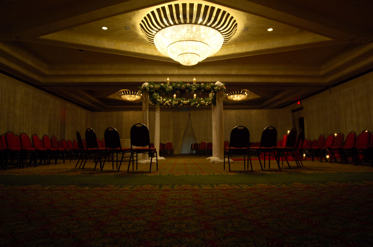 Four post arbor with white flowers and exotic greens inside a fully draped room with seating at three sides