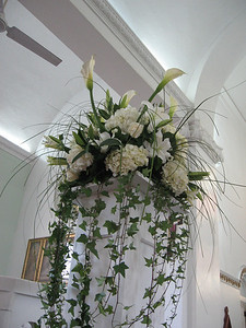 Loose arrangement of calla lilies, hydrangeas, and oriental lilies with flowing greens set a top tall column.