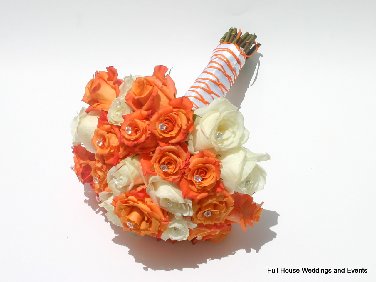 Bouquet - orange and ivory roses with white and orange satin wrap.