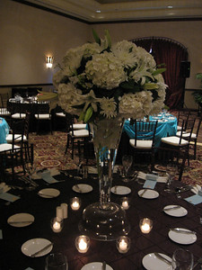 "Large centerpiece with white hydrangeas, casablanca lilies and chrysanthemums set atop a 27"" Marcel reversible trumpet vase with a submerge cymbidium orchid"