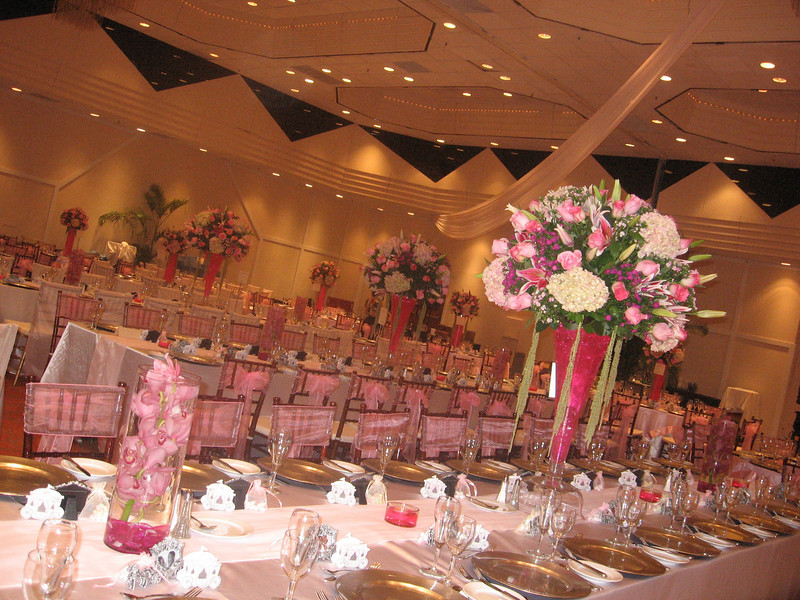 "Wedding Reception - Wyndham Nassau Resort Long Captain Tables draped in whiite satin cloths, silver lacquer chargers, mahogany chaivari chair with pink ties. Antique pink hydrangeas, pink roses and stargazer lilies set on top 27"" trumpet vase."