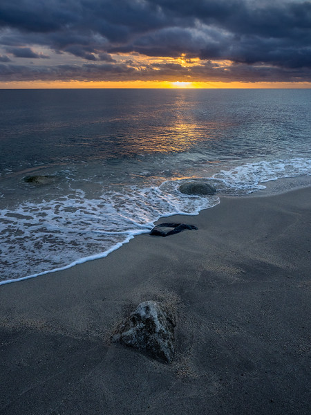 Small Crack of Light at Sunrise with Foam and Rocks