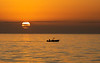 Fishing Boat Passing in Front of Rising Sun