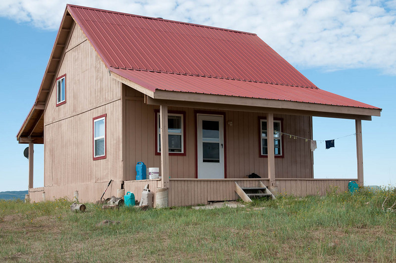 Cabin with a new coat of latex stain and some red trim on the windows and doors.