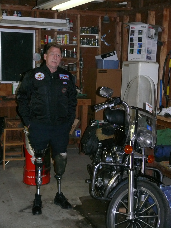 Dave in his garage in Bodfish with his current ride.  A Harley Davidson Sportster. Showing his prosthetic limbs.