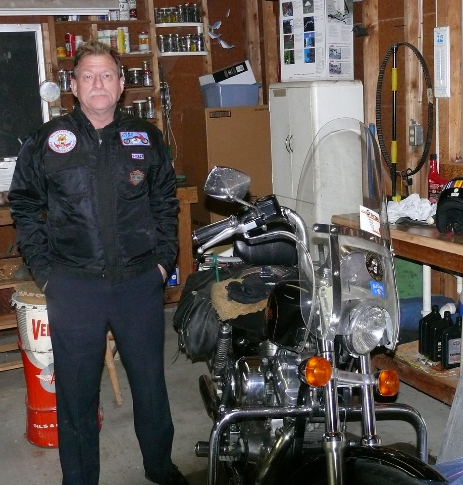 Barr posing in his garage with his Sportster pants legs down.