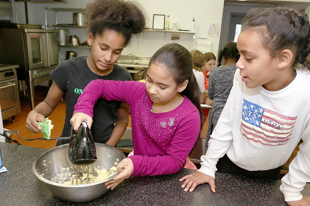 . Students at the Boys & Girls Club of North Central MA learned to make winning cranberry chip cookies with Program Instructor Sharon Jorgensen who the students called Chef Sharon. Isabella Williams, 10, from Fitchburg watches as Hashelyn Cabral, 12 on left, from Fitchburg and and Tais Lopez, 10, from Fitchburg mix up the batter for the recipe. SENTINEL & ENTERPRISE/JOHN LOVE