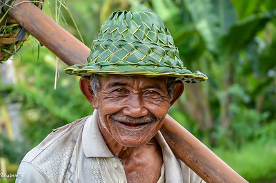 Balinese rice farmer in his traditional  hat woven from coconut leaves