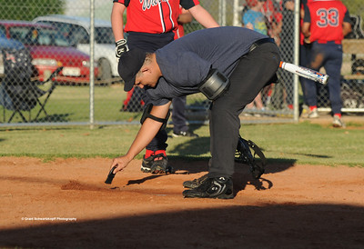 Umpire Jason Cuthbertson wipes home plate clean.