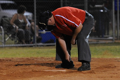 Umpire Peter Brown cleans the home plate