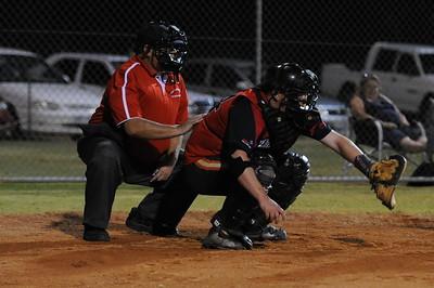 Umpire Peter Brown crouches behind  Matt Cutting (Berri) catcher
