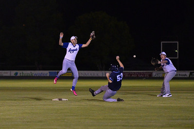 Jayden Perry (Renmark) jumps to grab the ball  as Stefan Best (Barmera) slides into base safely.