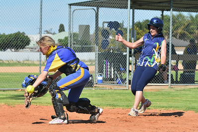 Chloe Passmore (Cobby) takes the ball as Julie Kent (Loxton) is about to touch home plate.