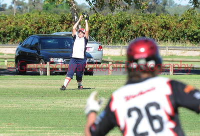 Brayden Murray (Waikerie) blurred in the foreground, watches as Taylee Healy (Berri) takes the catch to get him out.