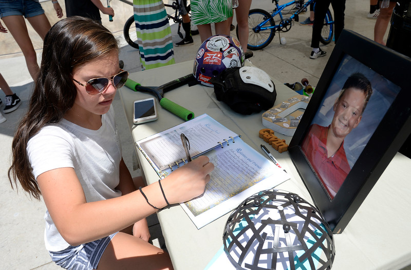 Celeste Bontz, 13, signs a guest book sitting on a table with a photo of Gavin Myers along with his scooter helmet  after friends and family release balloons in his memory Monday, July 2, 2018, at the skate park at Mehaffey Park in Loveland. Gavin, a 13 year-old who was killed when he was struck by a pick-up truck on June 8, spent countless hours at the skate park scootering with his friends.  (Photo by Jenny Sparks/Loveland Reporter-Herald)