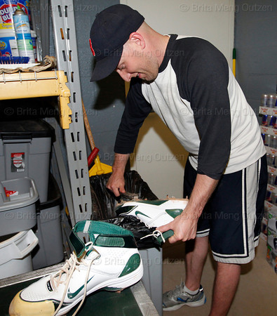 June 2, 2011, Boston, MA: A clubhouse worker uses a wire brush to cleans dirt off baseball cleats as the visiting clubhouse at Fenway Park is set up for the Oakland A's. Photos taken at Fenway Park from 7 PM to 1 AM during a shoot for the 100 Years of Fenway Park book project. (Brita Meng Outzen/Boston Red Sox)