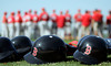 Boston Red Sox batting helmets lie on the grass as players hear instructions before live batting practice at Spring Training workouts in Fort Myers, Fla. on Thursday, February 19, 2009. (Brita Meng Outzen/MLB.com)