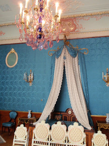 Blue bedroom with canopy and pink chandelier