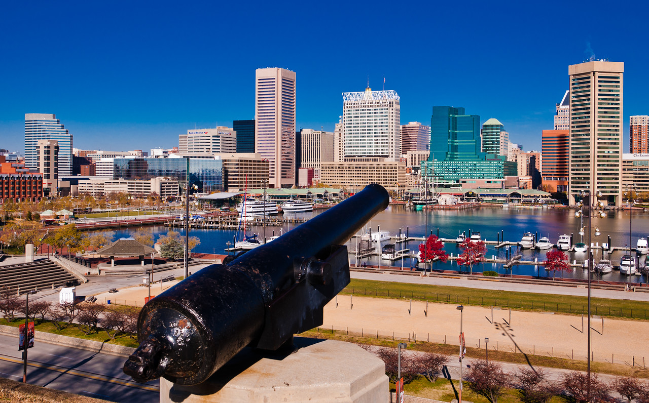 Cannon on Federal Hill, and a view of the skyline in Baltimore, Maryland.