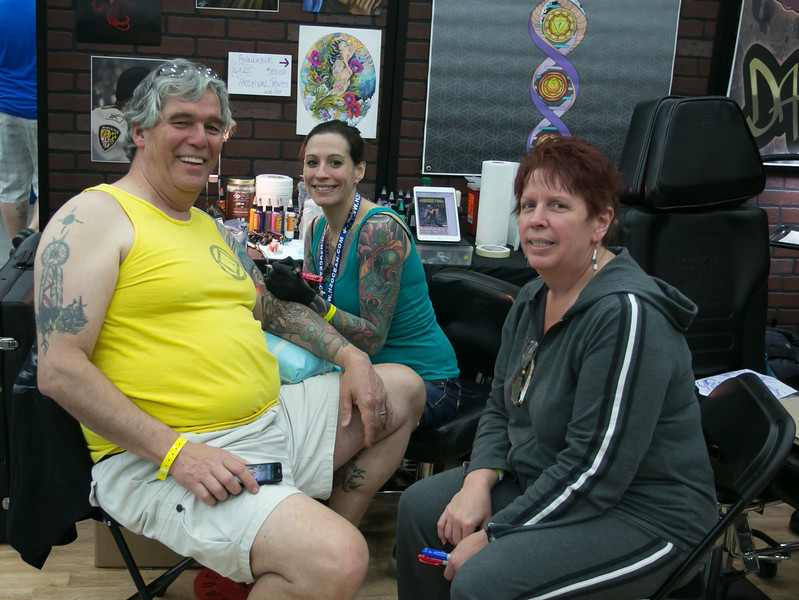 This is a family.  Daughter is tattooing Dad, Mom is watching.  A lovely family.