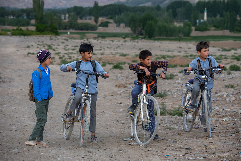 Boys with bicycles passing by one of Buddha caves in Bamyan.