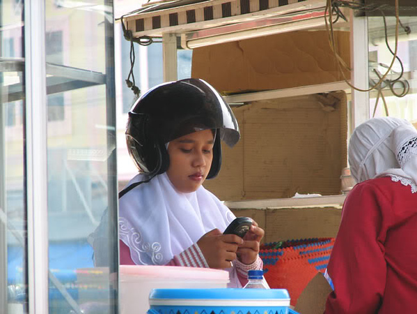 Everyone and I mean everyone, has a cell phone but they primarily use it to text message. Even the women were allowed phones. Also, the law requires helmets but no standard is set like there is here in the U.S. I saw a lot of army hats used and most people who did wear helmets never buckled them.