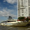 A ferry and an apartment block by the Chao Praya River in Bangkok, Thailand in June 2016