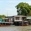 Houses and boats on the Chao Praya River in Bangkok, Thailand in June 2016