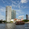 A Traditional Thai barge with tall apartment blocks as a backdrop seen on the Chao Praya River in Bangkok, Thailand in June 2016