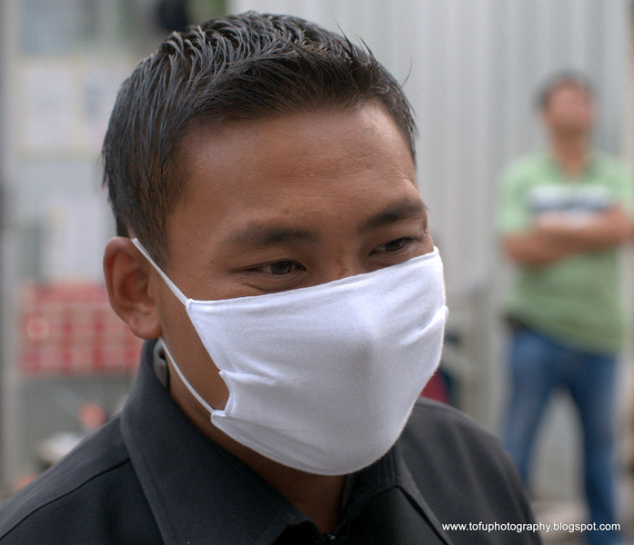 Man with a face mask  on Krung Thonburi road  in Bangkok, Thailand in December 2009