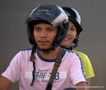 Couple on a motorbike by the Chao Praya River opposite the Saphan Thaksin BTS station, Bangkok, taken in December 2009