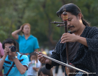Man taking a picture of the puppet master playing an instrument during the Jona Puppet show  at the International Street Show festival at Lumphini Park, Bangkok, Thailand in December 2009.