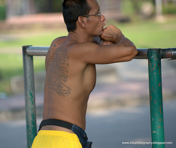 man with a big tattoo at Lumphini Park in Bangkok, Thailand, in December 2009