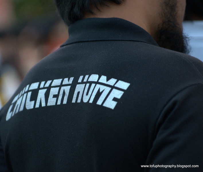 Man at the International Street Show in Lumphini Park, Bangkok in December 2009 with a t-shirt that says chicken home!