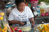 Woman in a flower stall in Silom, Bangkok, in December 2009. Her t-shirt says No job? NO problem, no car? NO problem