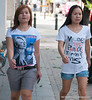 Two women walking in Silom, Bangkok, in December 2009. One t-shirt is of Paris Hilton, the other says Money is panacea for most girls